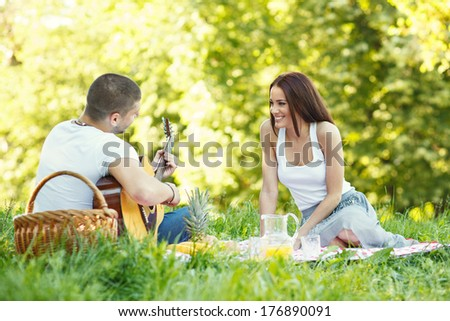Young man playing the guitar and flirting with a woman. Selective focus on woman. - stock photo