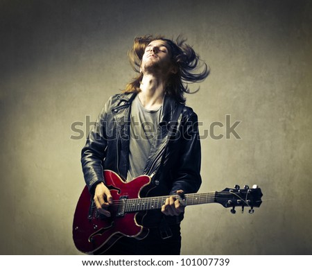 Young man playing the guitar and headbanging - stock photo