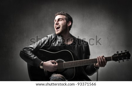 Young man playing the guitar and singing - stock photo