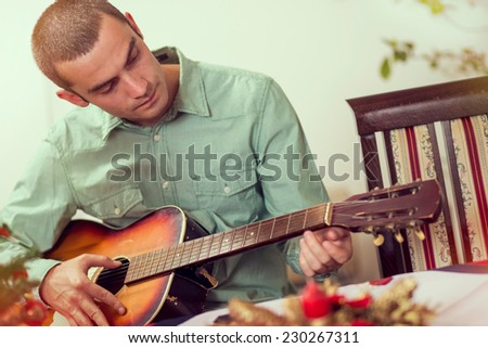 Young man playing the guitar at some private celebration event - stock photo