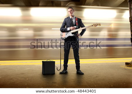 Young man playing the guitar in an underground station - stock photo