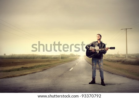 Young man playing the guitar on a countryside road - stock photo
