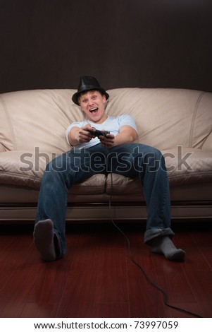 Young man playing video games on gray background - stock photo
