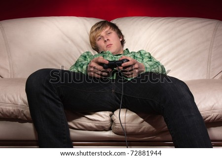 young man playing video games on red background