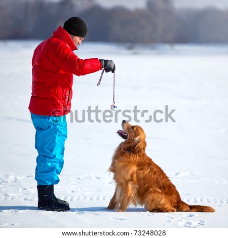 Young man playing with dog outdoors. - stock photo