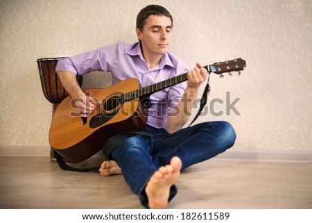 Young man playing with guitar at home