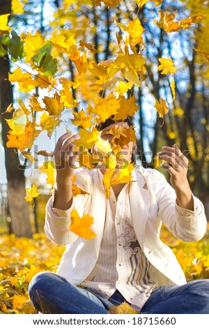 young man playing with leaves - stock photo