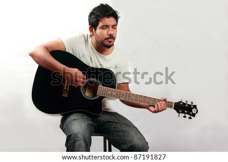 Young man plays a guitar - stock photo