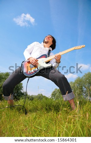 young man plays on guitar on grass - stock photo