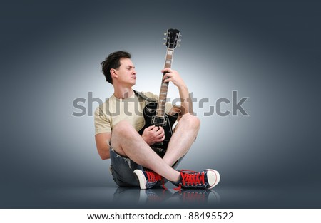 Young man plays the electric guitar, sound concept - stock photo