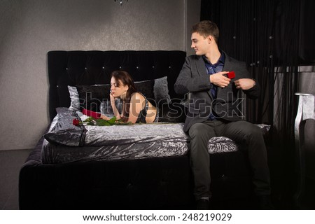 Young man plucking up courage to propose sitting on the end of the bed in his suit watching his girlfriend looking at her Valentines gift while removing the red ring box from his pocket - stock photo