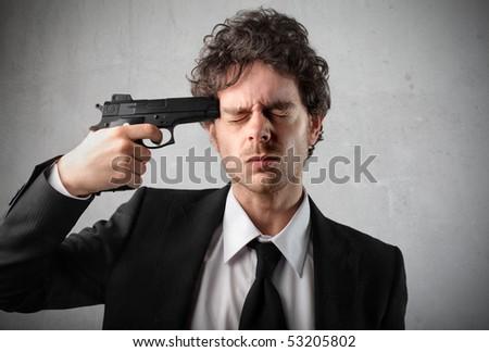 Young man pointing a gun at his head - stock photo