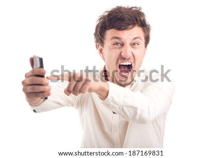Young man pointing at his cellphone, shouting - stock photo