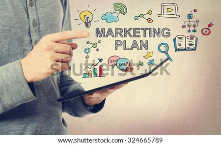 Young man pointing at Marketing Plan concept over a tablet computer - stock photo