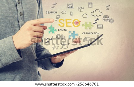 Young man pointing at SEO concept over a tablet computer - stock photo
