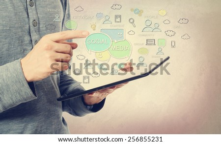Young man pointing at social media concept over a tablet computer - stock photo