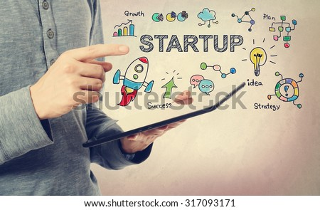 Young man pointing at Startup concept over a tablet computer - stock photo