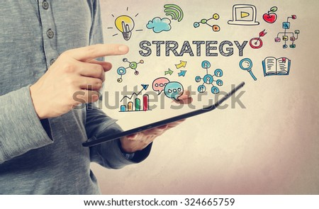 Young man pointing at Strategy concept over a tablet computer - stock photo