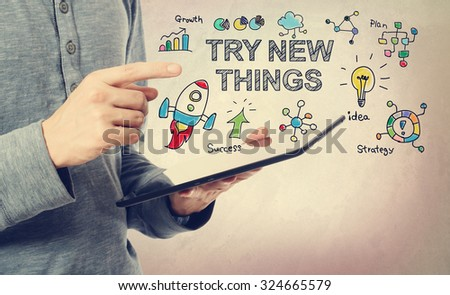 Young man pointing at Try New Things concept over a tablet computer - stock photo