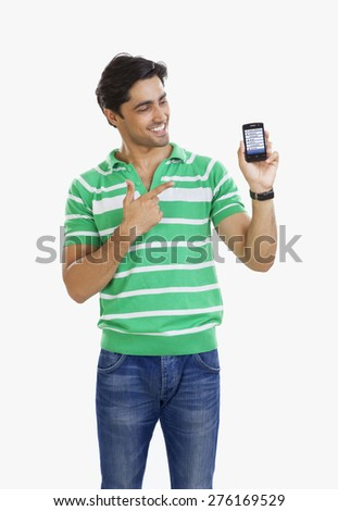 Young man pointing to mobile phone - stock photo