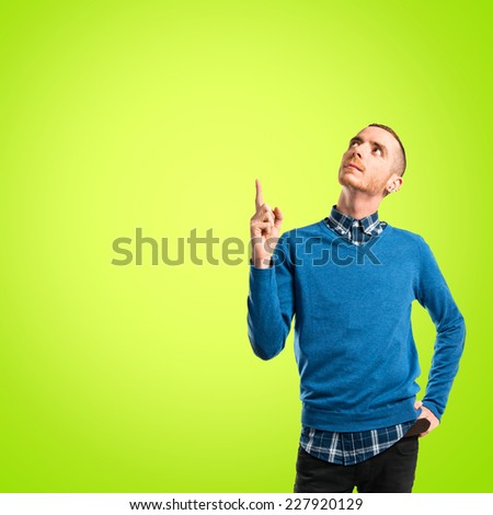 Young man pointing up over green background
