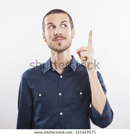 young man pointing up, showing something, having an idea - stock photo