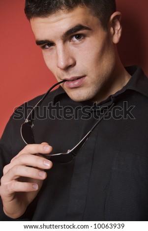 young man portrait, holding sunglasses, studio shot - stock photo