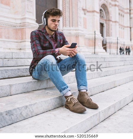 Young man portrait listening to music with headphones in front of San Petronio Cathedral in the city center of Bologna, Italy.