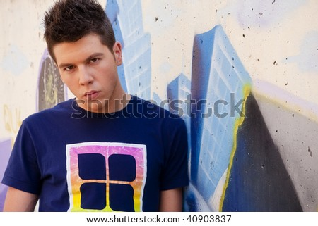 Young man portrait over grafted wall. - stock photo