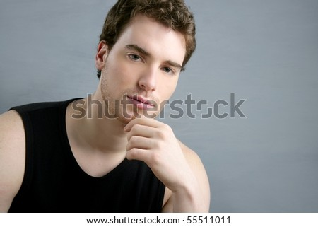 young man portrait posing looking camera over gray background - stock photo