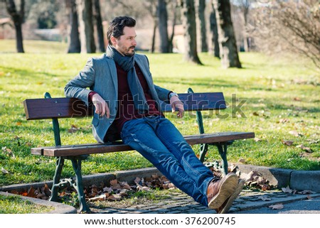 Young man portrait relaxing outdoor sit on a bench in a park. - stock photo