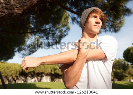 young man portrait stretching after jogging - stock photo