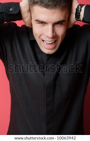 young man portrait with hands over ears - stock photo