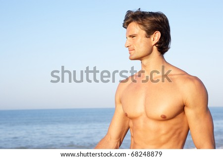 Young man poses on beach - stock photo