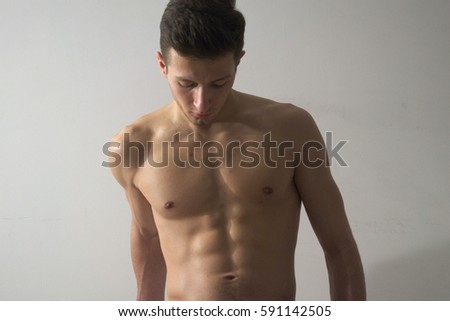 Young man poses on white background