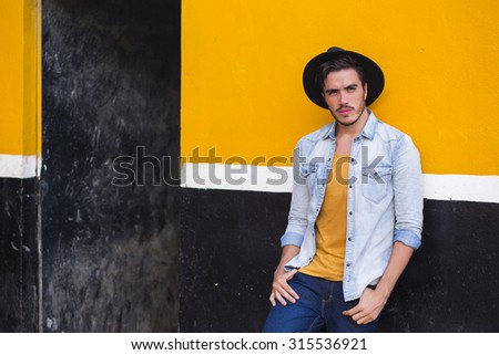 Young man posing in a urban background, with a cowboy style. - stock photo
