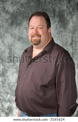 young man posing in front of portrait backdrop - stock photo