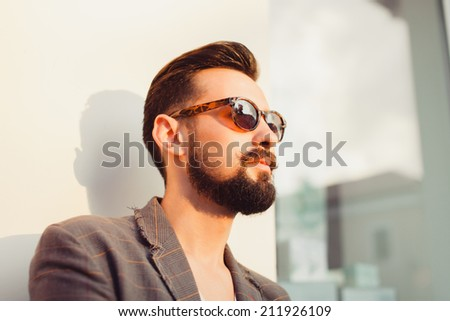 young man posing in the street, fashion style, vintage glasses, sunglasses, mustashe - stock photo