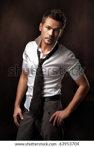 young man posing on dark background - stock photo