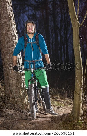 Young man posing on his ATB in the forest in the late afternoon - stock photo