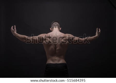 young man posing strong back muscles, rear view.