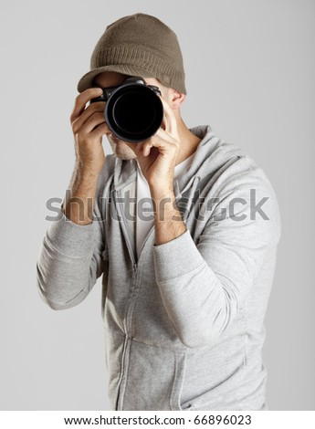 Young man posing with a photographic camera isolated on a gray background - stock photo