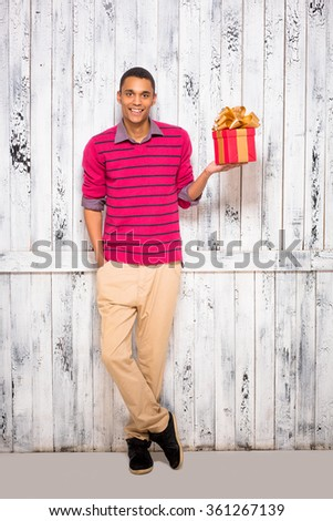 Young man posing with a present in studio - stock photo