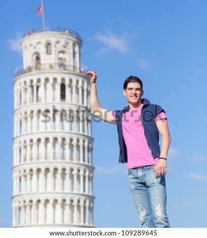 Young Man Posing with Leaning Tower in Pisa - stock photo