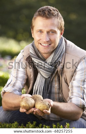 Young man posing with potatoes in garden - stock photo
