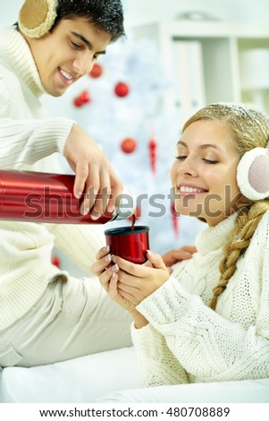 Young man pouring hot coffee of thermos for his girlfriend
