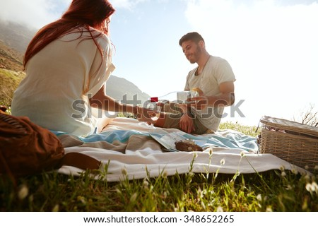 Young man pouring wine in glasses while sitting with his girlfriend. Young couple drinking wine and enjoying a picnic outdoors. - stock photo