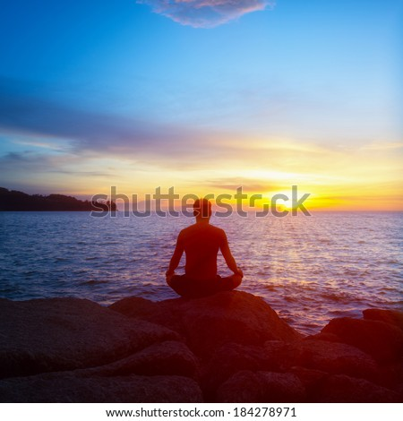 Young man practices yoga on the beach at sunset - stock photo