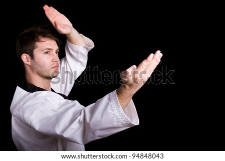 Young man practicing martial arts against black background - stock photo