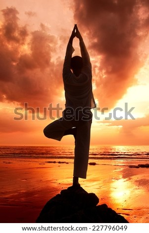 Young man practicing yoga at the beach. - stock photo